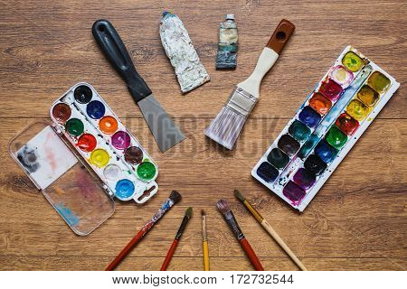 Artistic squirrel brushes tubes of oil paints and watercolors for art on a wooden background.The palette of twenty-four colors. Used tools for artists and schoolchildren. Tools for art. Set of artistic tools