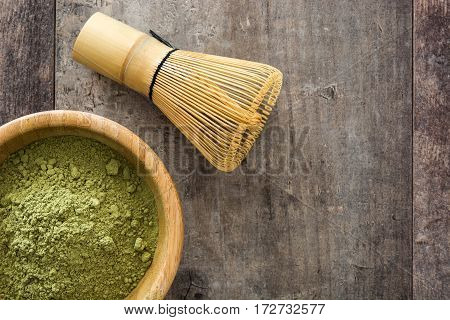 Matcha green tea in a bowl and bamboo whisk, on wooden background