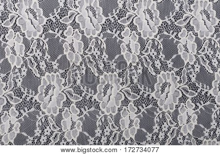 piece of white material with lace on black background