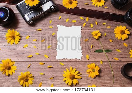 Old vintage camera lying on the wooden background. Film and three lenses lie on a table. Place for design on paper. Blank white sheet of paper. Yellow flowers and petals. A flower with a green stem.