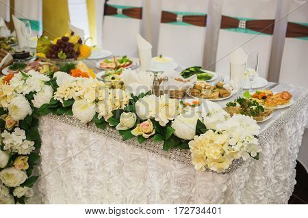 Decorated wedding table. Food on the table. Tableware. Empty glasses and wine glasses. Salad in a bowl. Table with food
