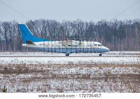 Kiev Region Ukraine - February 1 2011: Antonov An-140 regional passenger plane is taxiing after landing on a winter day