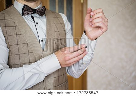 Man buttoning on the sleeve of his shirt. Zip up the cufflink. Men's style. Professions. The groom in a bow tie. Going to work to the meeting. Shirt with studs on the sleeves