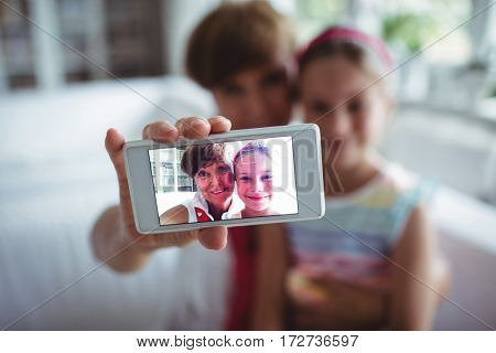 Grandmother and her granddaughter taking a photo from mobile phone at home