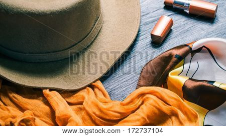 Fall season female accessories in natural shades. Felt hat, lipstick and necktie