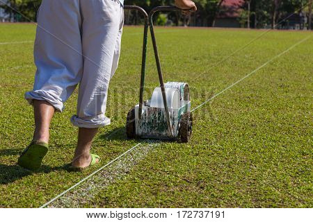 worker using paint tool to paint white line on soccer or football field on a sunny day