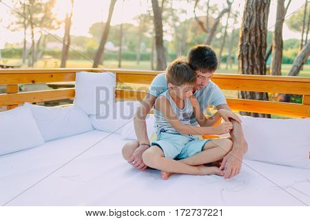 hot sunny day sitting on a wooden couch father and son in blue costumes