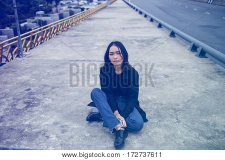 Asian ethnicity girl is on a bridge shoot.