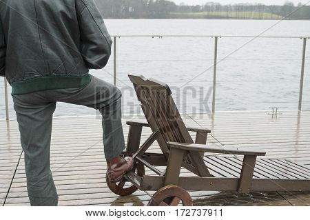 Man standing on a wet deck next to the beach lounger, outdoor rear cropped shot