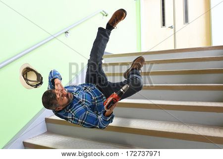 Hispanic worker falling on stairs while holding cordless drill