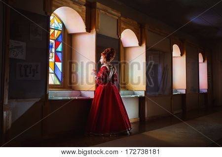 Queen of the museum. Red-haired girl with blue eyes in red dress. Queen with a high hairdo. Vintage image. A woman with pale skin
