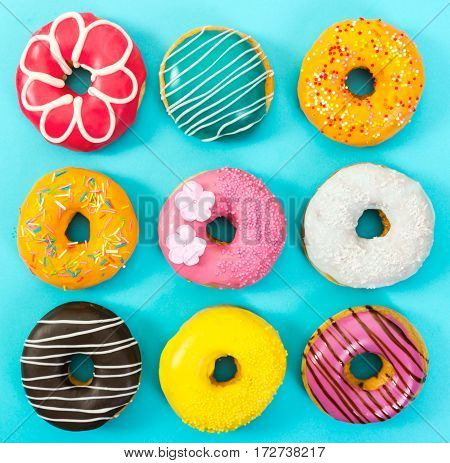 Various Colorful Donuts On Blue Background.
