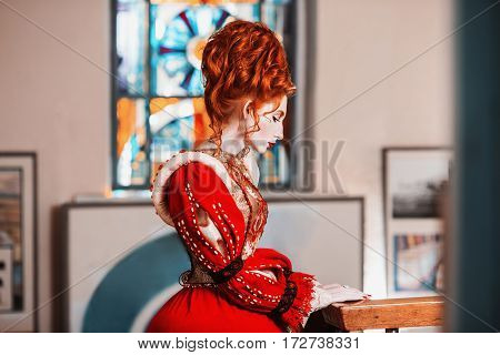 Queen of the museum. Red-haired girl with blue eyes in red dress. Queen with a high hairdo. Vintage image. A redhead woman with pale skin