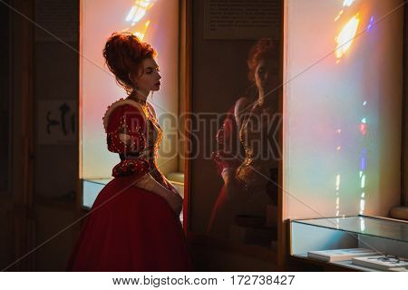 Red-haired girl with blue eyes in red dress. Queen with a high hairdo. Vintage image. A woman with pale skin. High hair in fashion style. The queen in a red dress on a background of a window