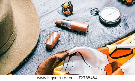 Still-life with womens accessories in natural shades. Felt hat and necktie, lipstick, ring and pocket watch