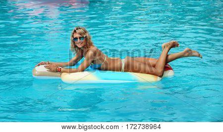 Young woman in the pool lying on mattress