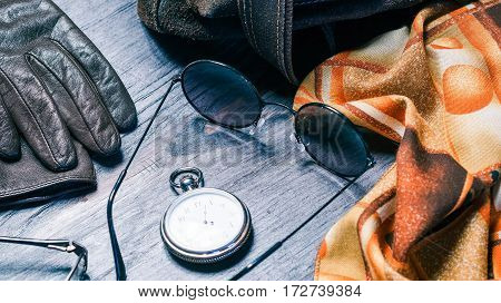 Fashion women accessories for cold sunny day. Sunglasses, pocket watch, leather gloves and necktie