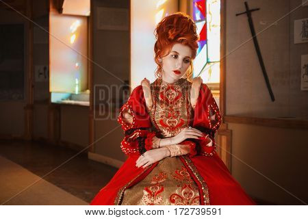 Red-haired girl with blue eyes in red dress. Queen with a high hairdo. Vintage image. A woman with pale skin. The queen in a red dress