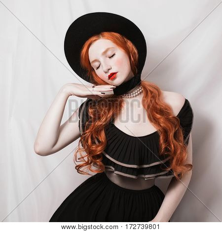 Redhead woman with red lips with a black hat with long hair. Bright unusual appearance. Redhead model