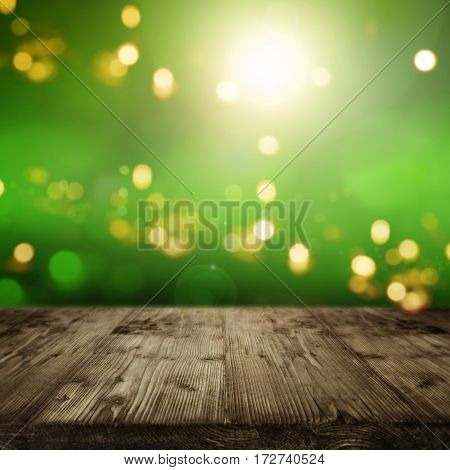 Green background with sun and bokeh in front of an empty old wooden table for a concept