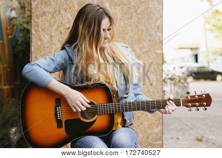 cheerfull blonde teenager playing acoustic guitar on the street