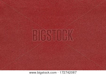 background and abstract grained texture of textile material or fabric of red color
