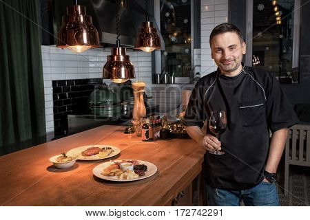 Chef cook, a man at the bar with a glass of red wine