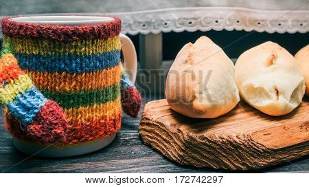 Mug in colorful sweater and homemade pies on rustic wood board