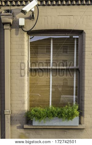 Close up on a window in a dark cream brick wall of a house protected with security cameras pointing to the left