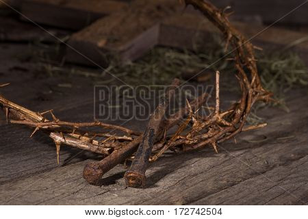 Closeup of crown of thorns and nails with wooden cross in background