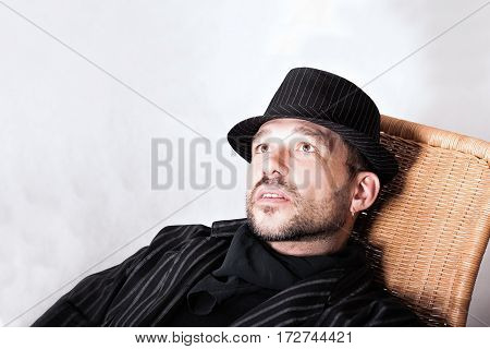 Portrait of handsome bearded man with pierced ear in black hat and cravat sitting in a chair.