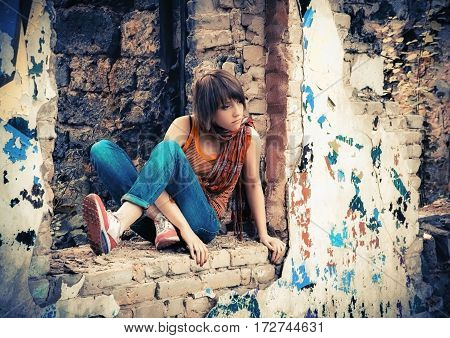 Young girl in an orange shirt and blue jeans sitting with a thoughtful look at the ruins of an abandoned brick building. Selective focus.