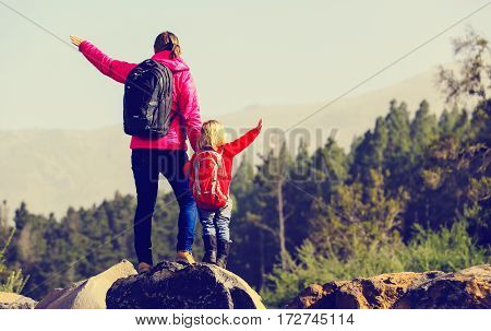 family travel- mother and little daughter hiking in scenic mountains