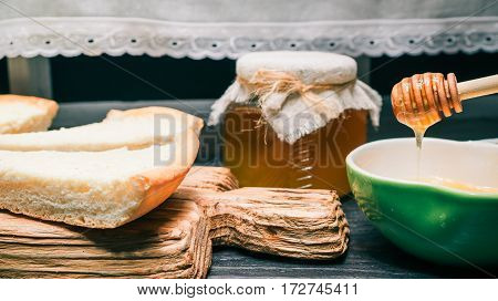 Honey in bowl with dipper and glass jar. Homemade cheesecake pieces on wooden serving board
