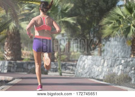 Healthy lifestyle young sporty woman running at tropical park