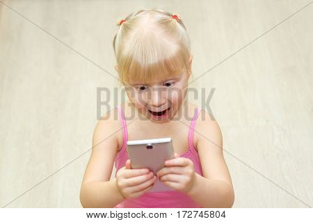 ittle girl in a pink dress scared with mobile phone