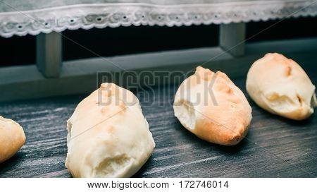 Homemade pies row on a black wood window sill. Wide angle closeup view