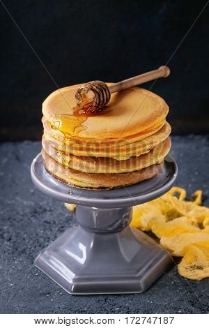 Stack of homemade american ombre yellow turmeric pancakes with honey sauce served on cake stand with wooden dipper over black stone texture background.