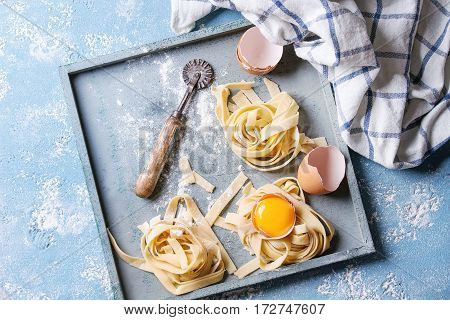 Fresh raw uncooked homemade twisted pasta tagliatelle with egg yolk, shell and pasta cutter in wooden tray with kitchen towel over light blue concrete background. Top view with space.