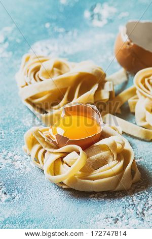 Fresh raw uncooked homemade twisted pasta tagliatelle with egg yolk, shell and pasta cutter over light blue concrete background. Toned image