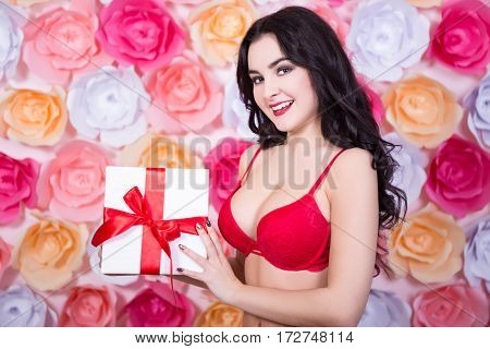 Spring Concept - Sexy Beautiful Woman In Red Lingerie With Gift Box Over Colorful Flowers Background