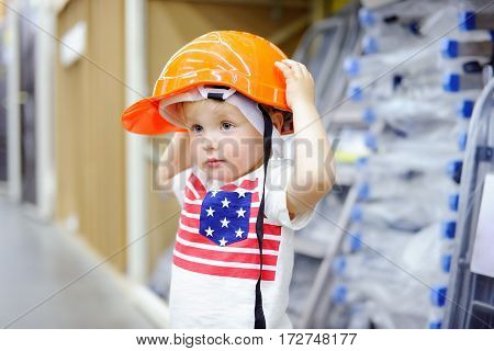Little boy having fun in a hardware store. Toddler builder choosing the right helmet in a hardware store. Childhood concept