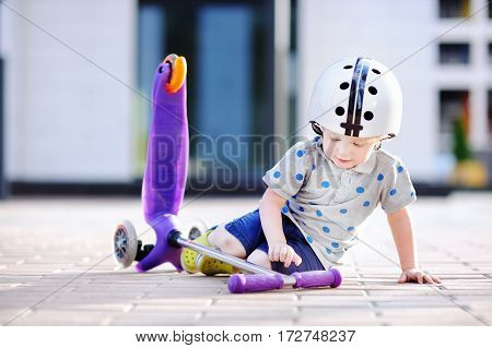 Toddler boy in safety helmet learning to ride scooter. Little child crashing during active outdoors game