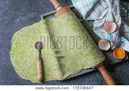Fresh homemade green spinach rolled dough for pasta tagliatelle on wood rolling pin with egg yolk and kitchen towel over dark gray background. Top view