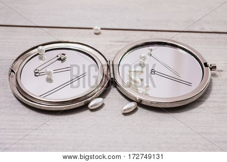 Double mirror pins needles and sewing items white beads on a light wooden background work of seamstresses. The pins on the mirror