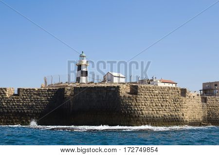 Old lighthouse with blue sky on the background in the city of Acre in Israel. View from the sea side