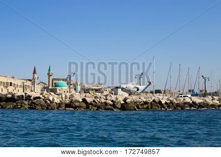 ACRE ISRAEL - CIRCA SEP 2016: Embankment in old arabic city Akko (Acre). Whale sculpture dome of the mosque and other buildings. Panoramic view from the sea side. Mediterranean sea