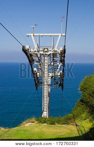 Metal construction of the ropeway over the sea. Hill covered with grace and blue sky