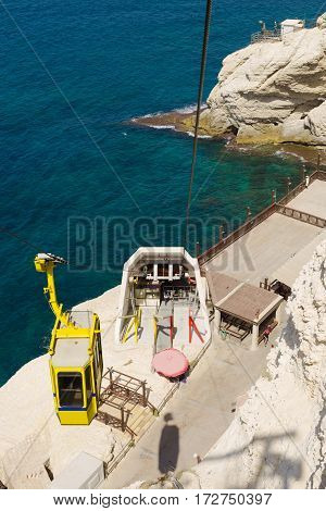 Ropeway above the grotto Rosh Hanikra and sea. Yellow cab goes down