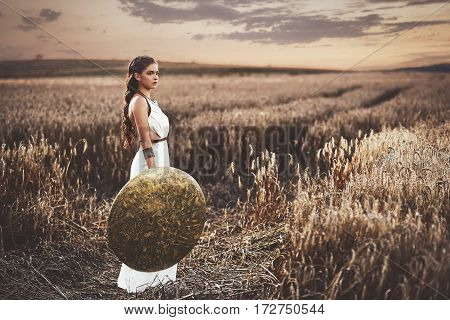 Full length of beautiful brunette woman with long hair wearing in white dress like greece style. Wife waiting husband after war, among grass in field holding iron shield in hand and looking away.